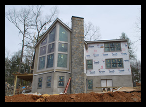 Contemporary new residence under construction in Albemarle County, Virginia, with large glass windows angled for view of river and mountains beyond, designed by Candace Smith Architect