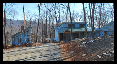 Modern new residence under construction in Albemarle County, Virginia, with guest cottage and stone chimneys, designed by Candace Smith Architect