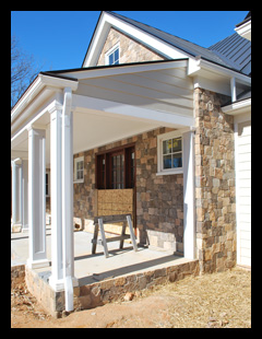 New residence under construction in Albemarle County, Virginia, with   custom front porch with fieldstone walls and bluestone flooring, designed by Candace Smith Architect