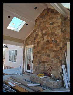 New residence under construction in Albemarle County, Virginia, with covered porch with fieldstone fireplace and walls, and skylights and beadboard ceiling designed by Candace Smith Architect