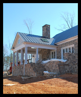New residence under construction in Albemarle County, Virginia, with fieldstone and custom rear porch and outdoor fireplace, designed by Candace Smith Architect